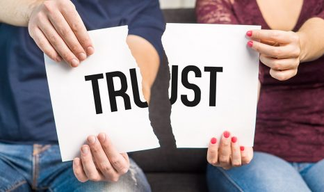 "Two people holding a paper with the word ""Trust"" torn in two"