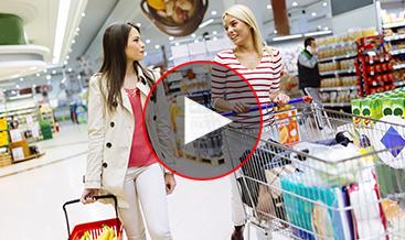 Two women talking in a supermarket shopping line