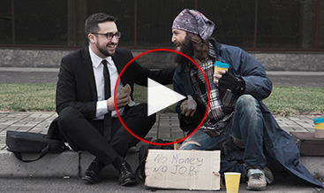 A business man sharing some time with a homeless man on the street