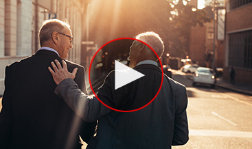 Two business men walking and chatting on the street