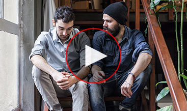 Two young men talking sitting at a house stairs