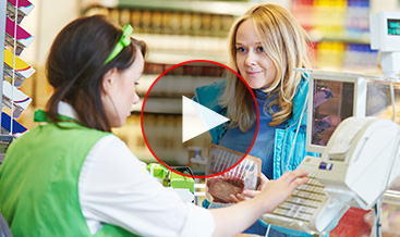 Women paying at a supermarket to a cashier woman