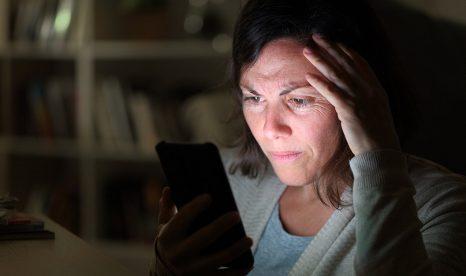 Woman worried watching news on her phone
