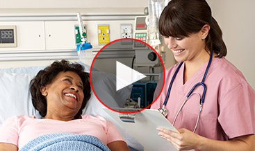 Woman at a hospital bed talking with a medical technician